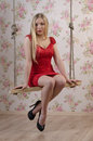 Woman in a red dress attractive sitting on swing against backdrop of wallpaper with roses Stock Photos