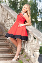 Woman in red dress beautiful young a s standing on an old stone staircase Royalty Free Stock Image