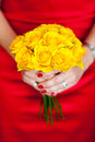 Woman in a red dress holding a yellow bouquet of roses Royalty Free Stock Photos