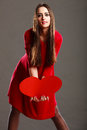 Woman in red dress holds heart sign