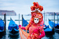 Woman in red dress masked for venice carnival in front of typical gondola boats traditional Stock Photo