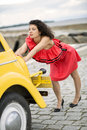 Woman in red dress pushing lightly car yellow Stock Images