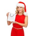 Woman in red dress with shopping bag sale gifts christmas x mas concept smiling and santa helper hat Stock Photo