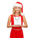 Woman in red dress with shopping bag sale gifts christmas x mas concept smiling and santa helper hat Royalty Free Stock Photo