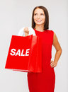 Woman in red dress with shopping bags sale gifts christmas x mas concept smiling Royalty Free Stock Image