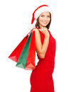 Woman in red dress with shopping bags sale gifts christmas x mas concept smiling and santa helper hat Royalty Free Stock Photo