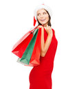Woman in red dress with shopping bags sale gifts christmas x mas concept smiling and santa helper hat Royalty Free Stock Photography