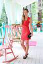 Woman in red dress standing near chair Royalty Free Stock Images