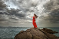 Woman in red dress stands on a cliff with a beautiful sea view a and dramatic clouds Royalty Free Stock Photo