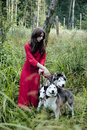 Woman in red dress with tree wolfs in forest brunette Stock Photos