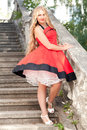 Woman in red dress young standing on the old stairs Stock Photos