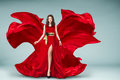 Woman in red fluttering dress sensual lonh evening Royalty Free Stock Photography