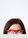 Woman in red framed eyeglasses looking away close up shot on light background Royalty Free Stock Photos