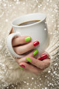 Woman with red and green nail polish holding cup of coffee in sweater seasonal a warm snow flakes border Royalty Free Stock Photography