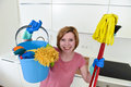 Woman with red hair in rubber washing gloves holding cleaning bucket mop and broom Royalty Free Stock Photo
