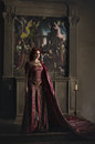 Woman with red hair wearing elegant royal garb and golden crown in ancient castle Stock Image