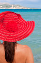 Woman with red hat looking at the sea beautiful alcudia beach mallorca spain Royalty Free Stock Photography
