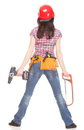 Woman in red helmet holding saw and drill female construction worker with belt of tools isolated on white background Royalty Free Stock Photos