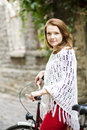 Woman in red hold tightly after bicycle wheel Stock Photos