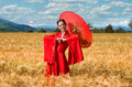 Woman in red kimono in the wheat field with chinese umbrella posing bright summer day Royalty Free Stock Image