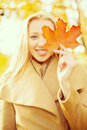 Woman with red marple leaf in the autumn park holidays seasons travel happy people concept smiling Royalty Free Stock Photos