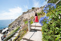 Woman in red at minack theater stands looking he the view open air ampi on july constructed on coastal cliffs Royalty Free Stock Images