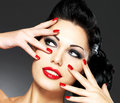 Woman with red nails and creative hairstyle beautiful fashion makeup model posing in studio Stock Image