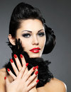 Woman with red nails and creative hairstyle beautiful fashion makeup model posing in studio Stock Photography