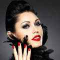 Woman with red nails and creative hairstyle beautiful fashion makeup model posing in studio Royalty Free Stock Images