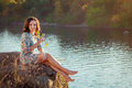 Woman with red rose beautiful brunette sitting on the cliff above the river holding at sunset Stock Images