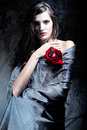 Woman with red rose in grey fabric Stock Photo