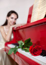 Woman and Red rose on red piano Royalty Free Stock Image
