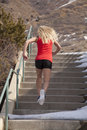 Woman red tank run up stairs snow a running the in the outdoors with all around her Royalty Free Stock Photo