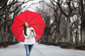 Woman with red umbrella walking in park in fall happy smiling multiracial girl cheerful central Royalty Free Stock Photo
