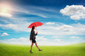 Woman with red umbrella walking smiley on green field over blue sky Stock Photos