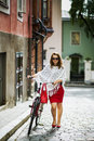 Woman in red walking on street with bicycle Stock Photography
