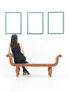 Woman reflecting on art back view of sitting a bench looking at empty frames displayed white wall Stock Photography