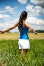 Woman rejoicing in the freedom of the countryside standing with her back to camera trendy summer shorts with her arms open Royalty Free Stock Images