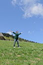 Woman rejoicing in the sunshine standing middle of a green mountain field with her arms outspread towards sun Royalty Free Stock Photo