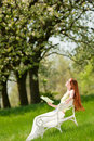 Woman relax under blossom tree in summer Stock Photo
