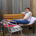 Woman relaxes on garden bench photo of a relaxing her with tea and biscuits photo taken th june Royalty Free Stock Photos