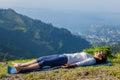 Woman relaxes in yoga asana Savasana outdoors Royalty Free Stock Photo