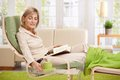 Woman relaxing in armchair at home reading book with feet up putting coffee on table smiling Stock Photo