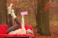 Woman relaxing in autumn fall park reading book. Royalty Free Stock Photo