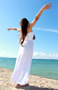 Woman relaxing at the beach with arms open enjoying her freedom wear long white dress Royalty Free Stock Image