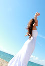 Woman relaxing at the beach with arms open enjoying her freedom wear long white dress Stock Images