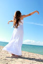 Woman relaxing at the beach with arms open enjoying her freedom wear long white dress Royalty Free Stock Images