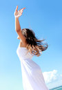 Woman relaxing at the beach with arms open enjoying her freedom wear long white dress Stock Image
