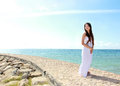 Woman relaxing at the beach with arms open enjoying her freedom wear long white dress Stock Photography