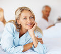 Woman relaxing on the bed with husband Stock Image